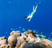 Boy swimming underwater. Teenage boy swimming underwater in shallow turquoise water at coral reef in Maldives Stock Photo
