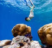 Boy swimming underwater. Teenage boy swimming underwater in shallow turquoise water at coral reef in Maldives Royalty Free Stock Image
