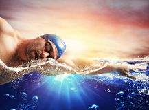 Boy swims in a blue deep water. During sunrise Stock Photo