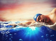 Boy swims in a blue deep water. During sunset Stock Photography