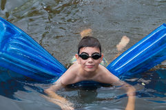 Boy swims on blue mattress in the river Stock Photos