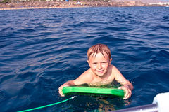 Boy swims with kickboard in the ocean Stock Photography