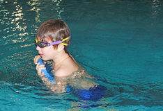 Boy swims in the pool. With the kickboard. A boy with glasses Royalty Free Stock Photos