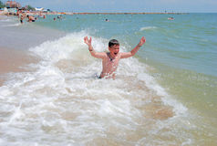 The boy swims in the sea. Of Azov on the Berdyansk spit Stock Photos