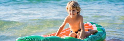 The boy swims in the sea on an inflatable mattress BANNER, LONG FORMAT stock photography