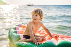 The boy swims in the sea on an inflatable mattress stock photography