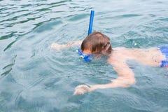 Boy swims in sea in scuba gear. Royalty Free Stock Photography