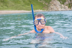 Boy swims in sea a mask for scuba diving. Royalty Free Stock Image