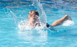 Boy swims with a splash in the water park.  stock photography