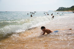 Boy swims in the surf. In the background, people are not in focus Stock Images