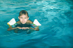 Boy swims in swimming pool during a swimming lesson. Child swims in swimming pool during a swimming lesson Stock Image