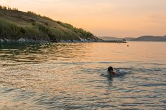 Boy swims to shore at dusk royalty free stock photo