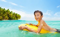 Boy swim on body board in the sea and smile. Boy swims in the water body board in the sea near tropical island with big smile Stock Image