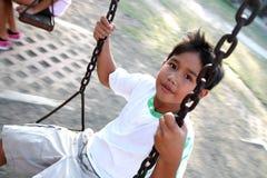 Boy on a swing. Asian kid enjoying a swing ride Stock Images