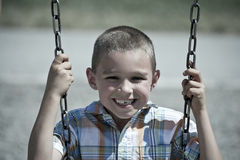 Boy on Swing. Young Boy smiling while swinging on swing Stock Images