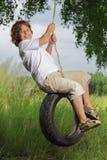 Boy on swing. Happy boy on swing outdoors Royalty Free Stock Image