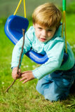 Boy in swing. Boy with funny face playing in a swing Stock Photography