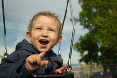 Boy on swing. Pointing on something royalty free stock photos