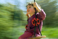 Boy on swing. Smilling boy on a swing with motion blur Stock Images