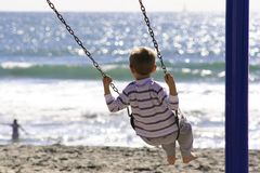Boy on swing. Beach playground. Swinging on the beach in Oceanside, California Stock Images