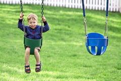 Boy in swing stock image
