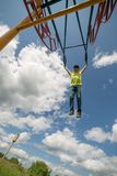 The boy on a swing against the blue sky. The boy in the clouds. Bright emotions. Clouds in the sky, summer sunny day royalty free stock photography