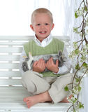 Boy on Swing Holding Bunny. Young boy in green on swing holding bunny Stock Photos