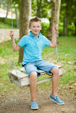 A boy on a swing ina late summer afternoon Royalty Free Stock Images