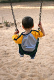 Boy On A Swing At The Park Stock Photo