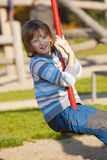 Boy on a Swing in the Playground Stock Images