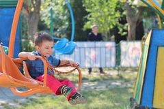 Boy in swing ride. A happy smiling three year old boy having fun on an unsafe loosely buckled swing ride in the summer Royalty Free Stock Images
