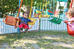 Boy in swing ride. A happy smiling three year old boy having fun on an unsafe loosely buckled swing ride in the summer Stock Image