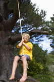 Boy (9-11) on swing, smiling, low angle view Stock Photography