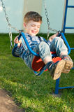 Boy on swing. Three year old  boy on swing. He is wearing orthopedic shoes Royalty Free Stock Image