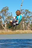 Boy swinging. A boy is swinging on a rope over a river in summer Royalty Free Stock Images
