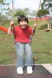 Boy swinging. Happy boy swinging happily at the playground in the park Royalty Free Stock Image