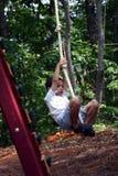 Boy Swinging. Boy swings on a playground Royalty Free Stock Photos