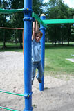 Boy swinging from a bar in a park Stock Photography