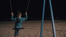 Boy swinging in the evening and looking at dark sea stock footage