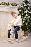 Boy swinging on the horse New Year Christmas. The boy swinging on the toy horse New Year Christmas Royalty Free Stock Photo