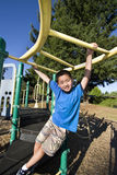Boy Swinging on Jungle gym - Vertical Stock Image