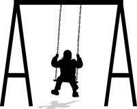 Boy swinging at the park in winter jacket Stock Images