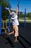 Boy swinging on rings. In outdoor playground Royalty Free Stock Photos