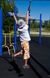 Boy swinging on rings royalty free stock photos