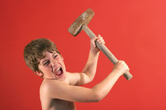 Boy swinging sledge hammer Stock Image