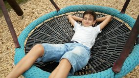 Boy swinging on a swing a hammock on the amusement park in the city. 4k, copy space stock video