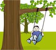 Boy swinging from tree Stock Image