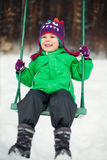 Boy swinging in winter park Stock Photos