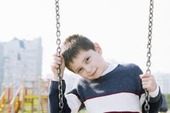Boy on swings Stock Image