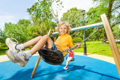 Boy swings in opposite direction to the girl Royalty Free Stock Photos